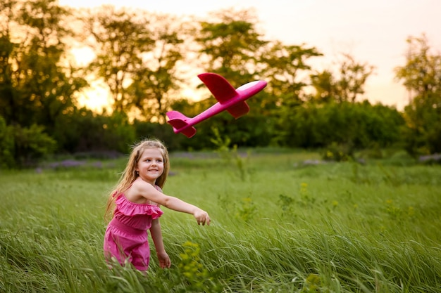 The baby launches a pink airplane on the background of the forest and tall grass. playing with a pink plane wearing a pink suit