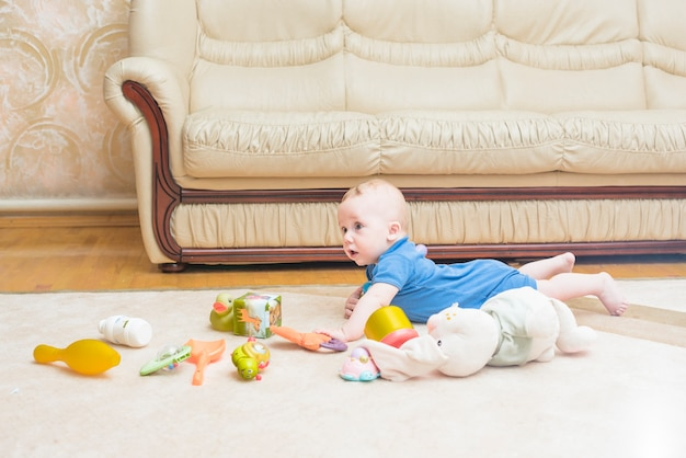 Baby laying with many toys on carpet at home