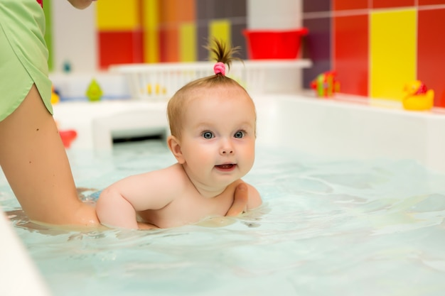 Baby learn swimming, infant swimming, healthy family mother teaching baby swimming pool