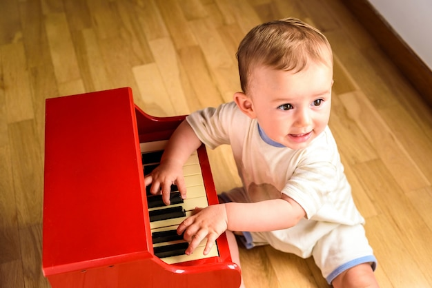 Baby learning to play the piano with a wooden toy instrument, a tender and funny childhood scene.