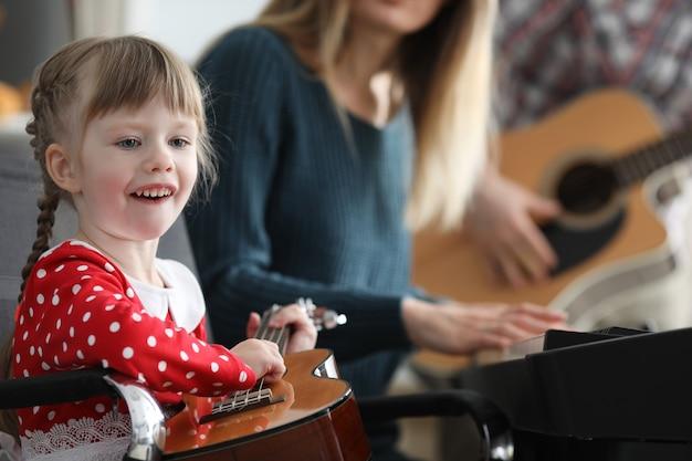 Малыш учится играть на музыкальных инструментах с родителями