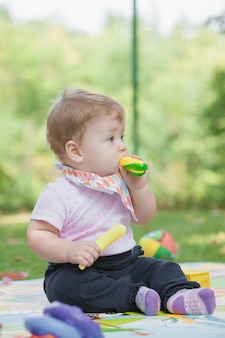 Малышка младше года играет с игрушечным бананом