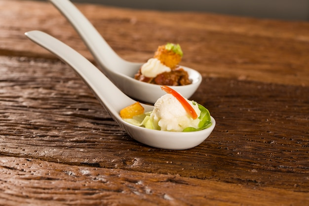 Салат из детского салата, помидоры черри, сердечки пальм, соус из цветной капусты, жареный маниок и соленые взбитые сливки в ложке. вкус гастрономической еды руками