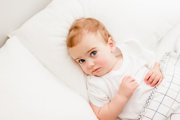 赤ちゃんは枕の上に横たわって見上げる