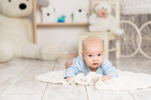 아기는 장난감, 개발 개념, 게임을 갖춘 어린이 방에 집에 누워 있습니다.