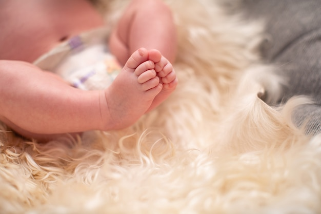 Baby lies on natural wool, the skin of the animal blond. cute baby feet closeup of christmas. selective focus. a lot of free space for writing text.