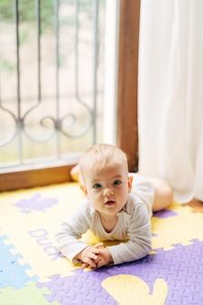 아기는 창 배경에 대해 바닥에 컬러 깔개에 자신의 배에 누워