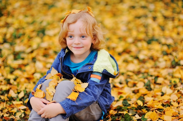 Baby - little boy with curly blond hair smiling against yellow autumn leaves in the park