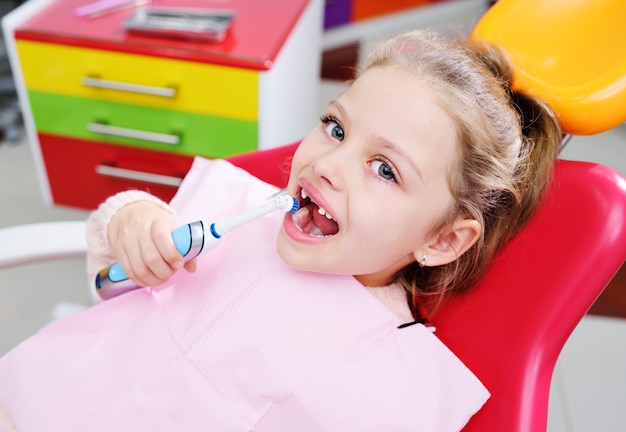 Baby little cute girl without front milk teeth in red dental chair with electric automatic toothbrush in hands.