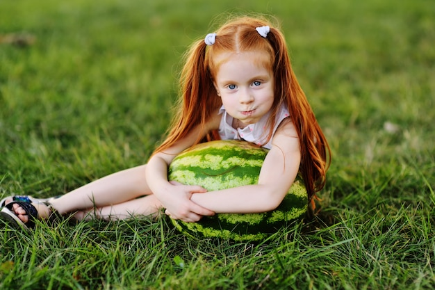 Baby little funny girl with red hair leaning on a huge watermelon in the park on the grass on a summer day