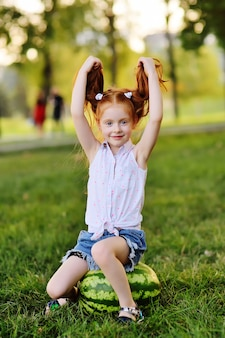 Baby little funny girl with red hair leaning on a huge watermelon in the park on the grass