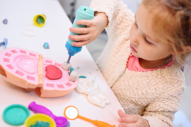 Baby little girl playing in dentist - makes plasticine teeth and brushes artificial jaw