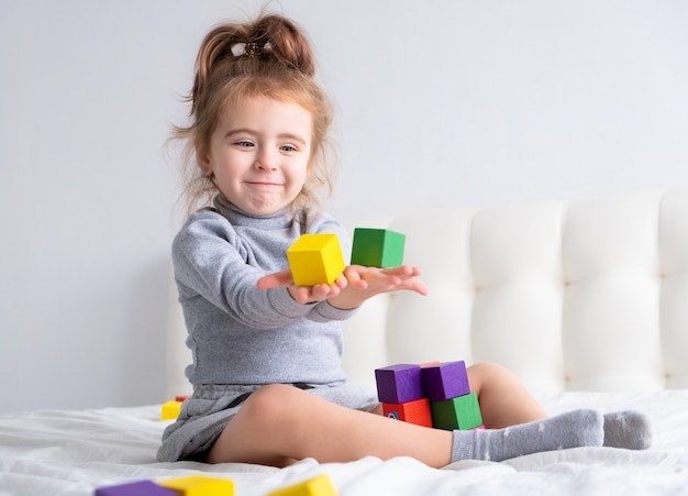 Baby little girl playing wooden toys at home on bed. home activities for kids.