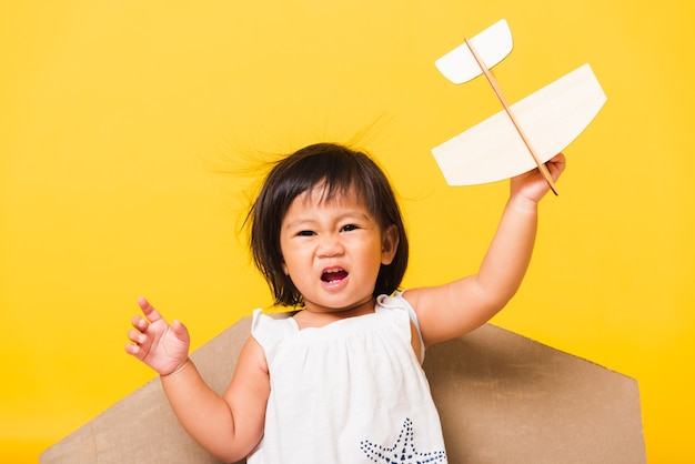 Baby little girl with toy cardboard airplane