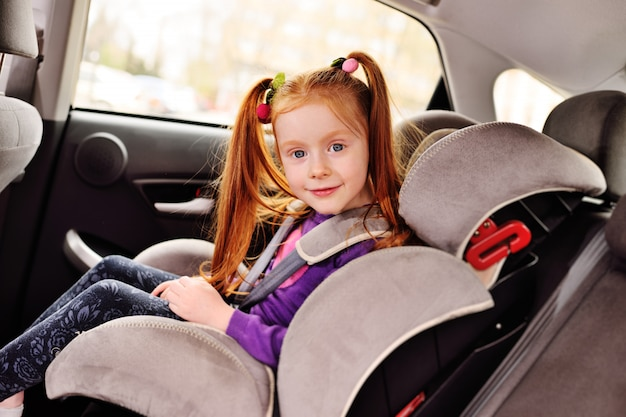 Baby little red-haired girl smiling while sitting in a child car seat.