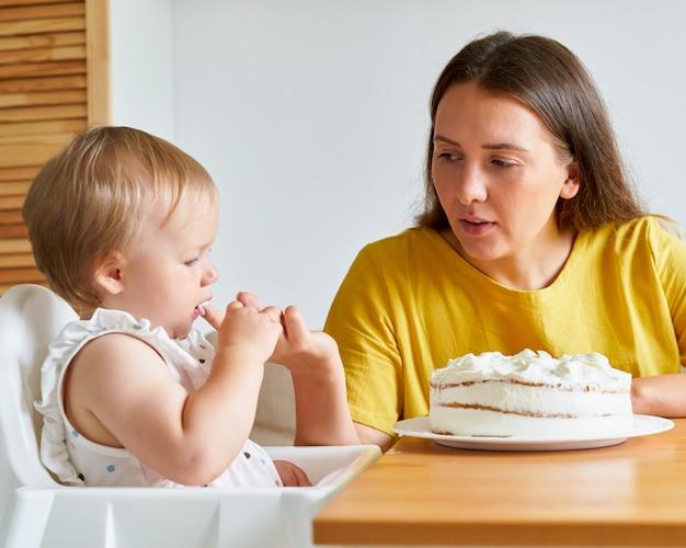 Младенец с интересом смотрит на кремовый торт и сосет палец, мама помогает дочери съесть пирог