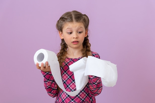 Baby looks at a roll of toilet paper isolated on purple background.