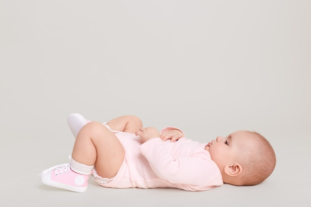 Baby lying on back on floor while posing isolated over white wall. infant wearing pale pink bodysuit and tiny sneakers, little kid playing indoor alone.