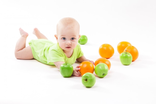 Baby lying on the background and smiling among fruit