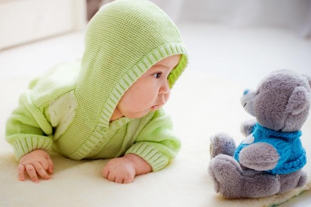 Ребенок лежит и смотрит на игрушечного медведя