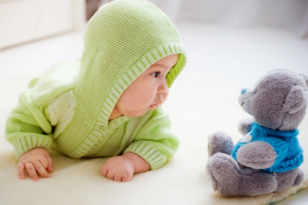 Baby lying down looking at toy bear