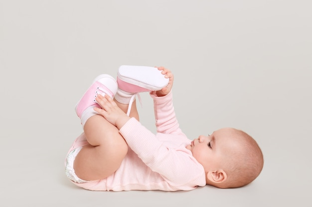 Baby lying on floor and playing with her feet, charming infant wearing pink bodysuit and shocks indoor, cute kid isolated over white wall.