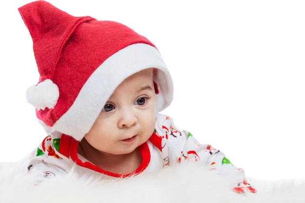 Baby lying on his stomach in a santa claus hat with a surprised