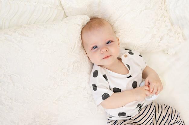 テキストのための場所のミルクのボトルとパジャマで自宅のベッドに横たわっている赤ちゃん