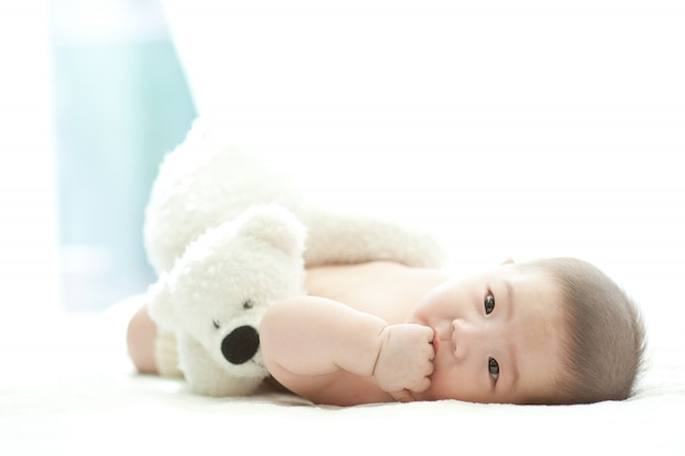 A baby lying on a white bed with a white background is smiling at the front.