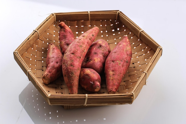 Baby mini red sweet potato on bamboo wooven basket plate.  isolated on white background. copy space for text