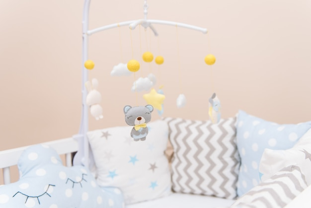 Baby mobile with different toys in the form of animals and stars, felt toys in crib