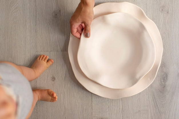 Baby and mom with white ceramic dishes on wooden background