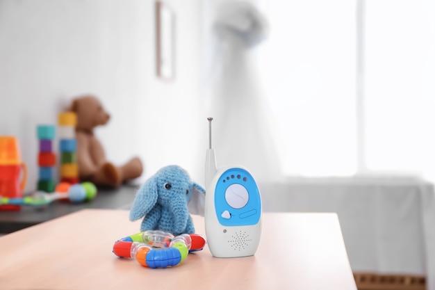 아기 모니터, 딸랑이 및 방에있는 테이블에 장난감. 라디오 유모