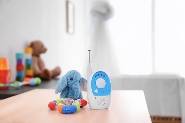 Baby monitor, rattle and toy on table in room. radio nanny