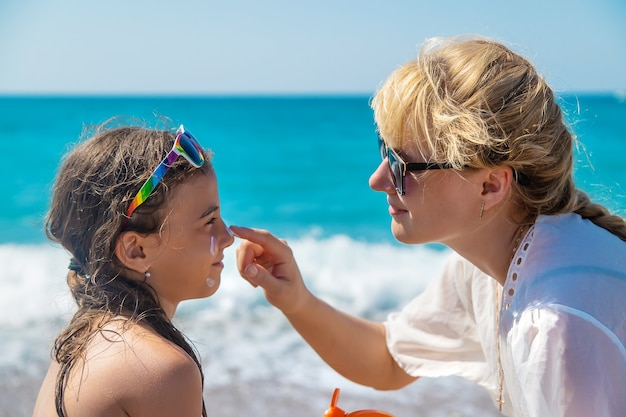 The baby and the mother are putting sunscreen on their face. selective focus.