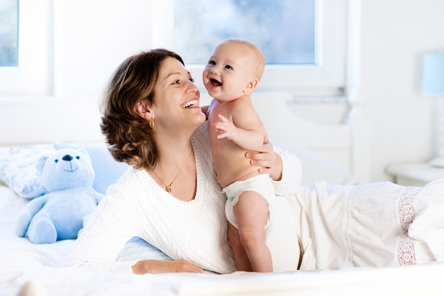 Baby and mother at home in bed. mom and child.