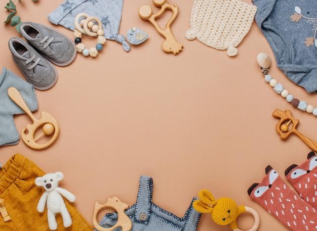 赤ちゃんの天然素材のアクセサリーのコンセプト。テキスト用の空白のあるベージュの背景に木のおもちゃ、服、靴。上面図、フラットレイ。