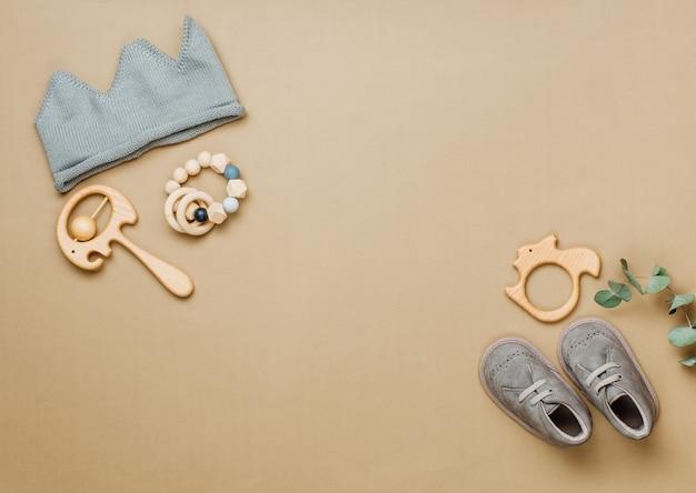 赤ちゃんの天然素材のアクセサリーのコンセプト。木のおもちゃ、ニットの王冠、テキスト用の空白のあるベージュの背景の靴。上面図、フラットレイ。