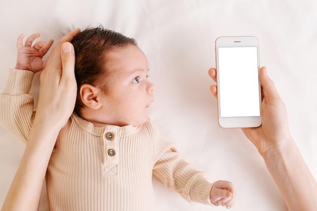 手に白い画面で携帯電話を保持している白いベッドの上の赤ちゃん新生児