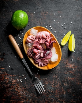Baby octopus on plate with ice and chopped lime on dark wooden table