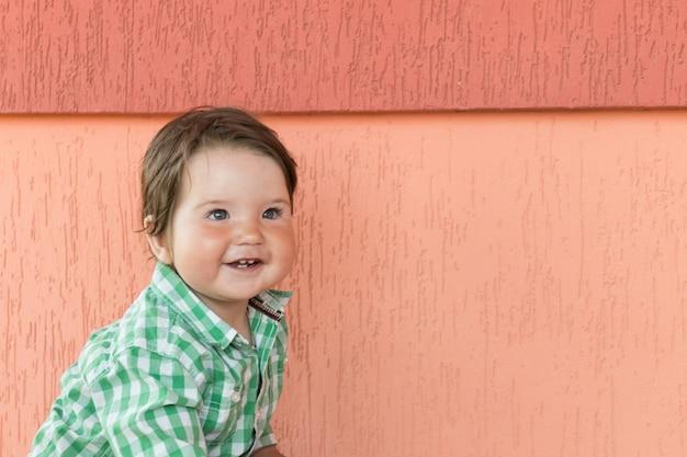 Ребенок на коралловой стене. маленький мальчик. в клетчатой зелено-белой рубашке.