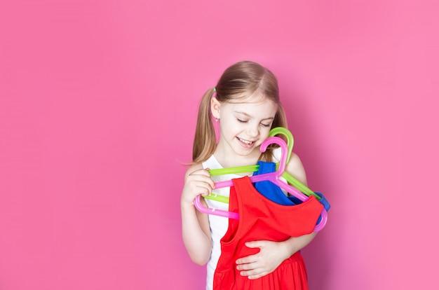 분홍색 벽에 아기, 어린 소녀는 서로 다른 색상의 두 드레스를 보유하고 하나의 가격에 두를 구입에 기뻐