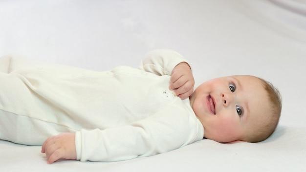 白い背景の上の赤ちゃんは笑顔で横たわっています。セレクティブフォーカスチャイルド。