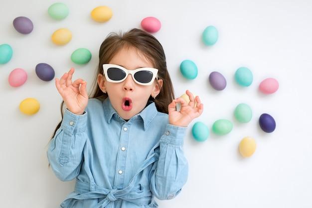 Ребенок на белой стене с пасхальными яйцами