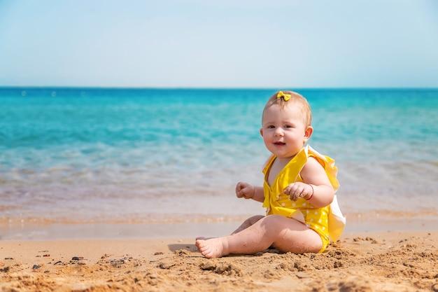 黄色いベストと海の近くのビーチで赤ちゃん