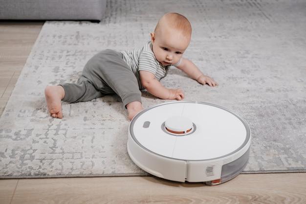 Ребенок на полу с роботом-пылесосом. бытовая техника для семьи с детьми, которая облегчает жизнь маме. автономная уборка ковров, ковриков, современный прибор для дома с детьми.