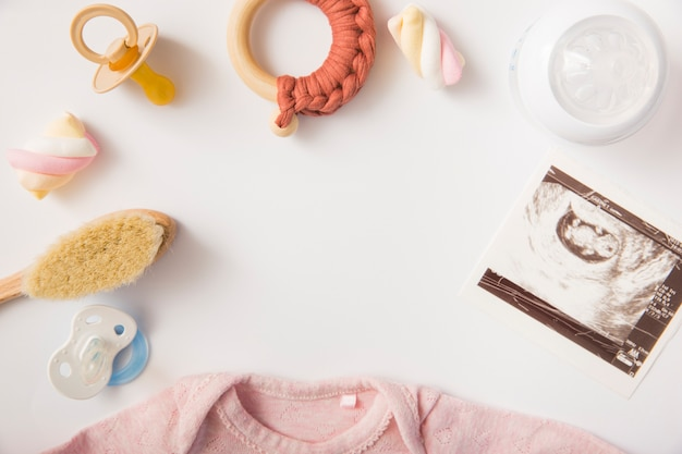Соска; зефир; щетка; игрушка; бутылка молока; изображение сонографии и baby onesie на белом фоне