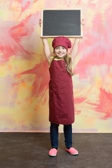 Ребенок или счастливый ребенок с баннерной доской на кухне или в ресторане на абстрактном фоне, еда и покупки, мода и дизайн, бизнес и маркетинг