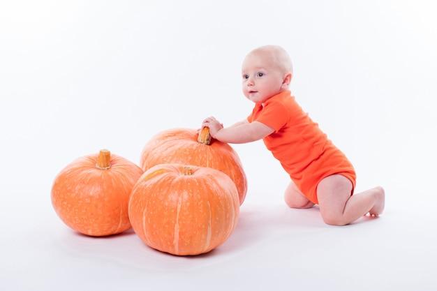 Baby in orange tshirt on white tshirt sits next to pumpki