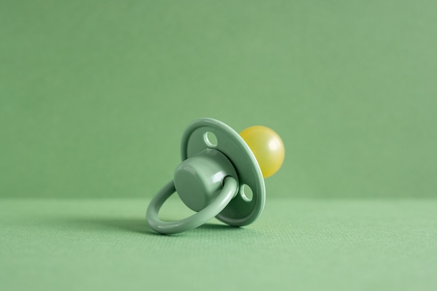 Baby pacifier on a green background, place for an inscription side view